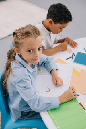 high angle view of caucasian kid looking at camera while sitting near african american classmate at table in classroom
