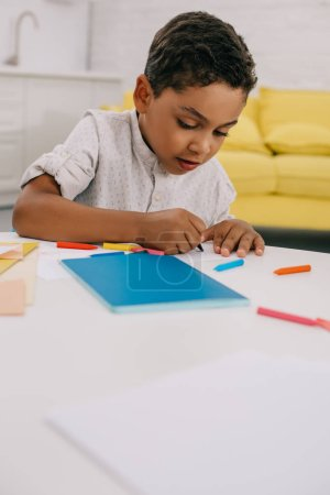 portrait of african american boy drawing picture with colorful pencils at table in classroom