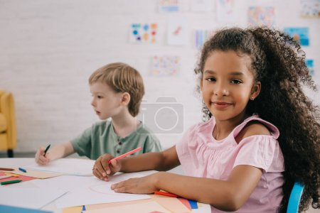 selective focus of multicultural preschoolers at table with papers and pencils in classroom