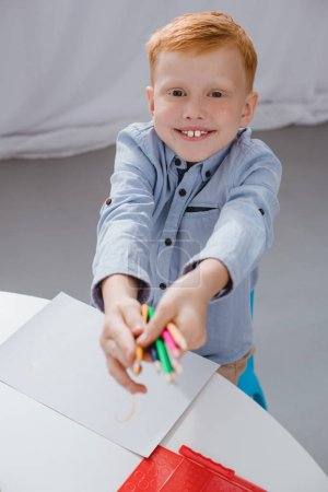 Photo for Cheerful preschooler red hair boy with pencils sitting at table with paper for drawing in classroom - Royalty Free Image