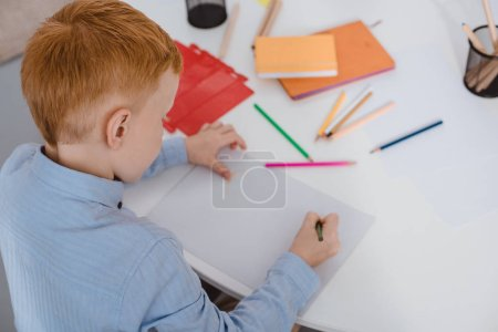 high angle view of red hair boy drawing picture with pencils at table