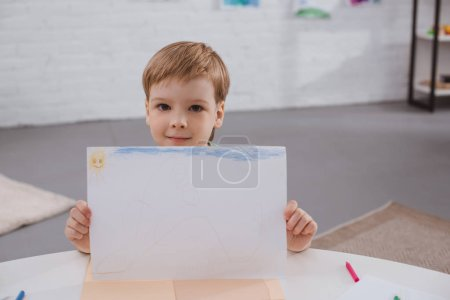 portrait of cute boy showing picture in hands at table in classroom