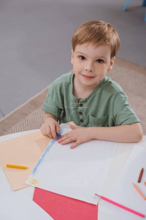 high angle view of preschooler boy sitting at table with paper and colorful pencils for drawing in classroom