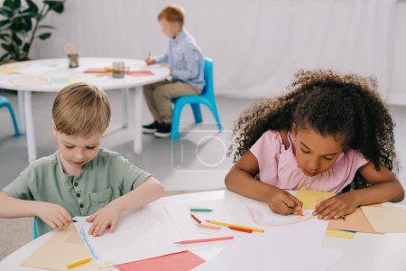multicultural preschoolers drawing pictures with pencils in classroom