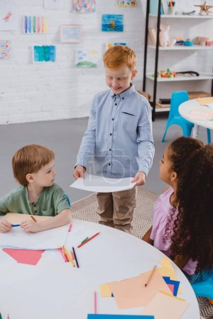 adorable multicultural kids with papers in classroom