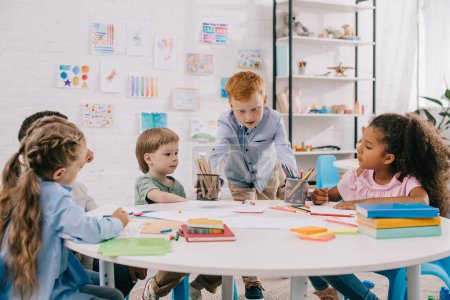 interracial kids sitting at table with papers and paints for drawing in classroom