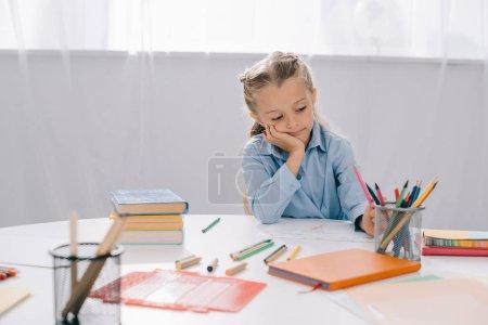 Portrait de fillette dessin avec des crayons colorés à table