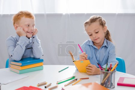 portrait of smiling red hair boy looking at classmate writing in notebook in classroom