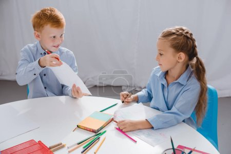 portrait of cute preschoolers drawing pictures at table with in classroom