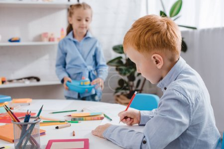 selective focus of red hair boy drawing picture while classmate standing near by at table