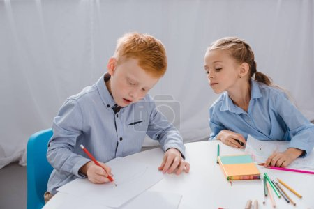 portrait of adorable kids drawing pictures at table in classroom
