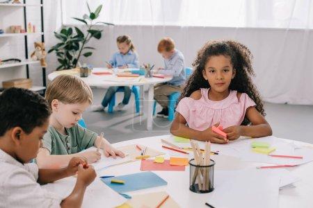 Photo pour Enfants d'âge préscolaire multiculturelles dessiner avec des crayons dans la salle de classe - image libre de droit