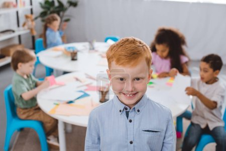 selective focus of happy red hair boy looking at camera with multiracial classmates behind in classroom