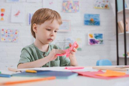 niño lindo con papel rosa sentado en mesa de salón de clases