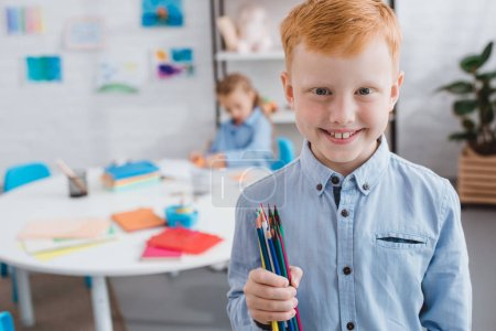 selective focus of happy red hair boy with pencils and classmate at table in classroom