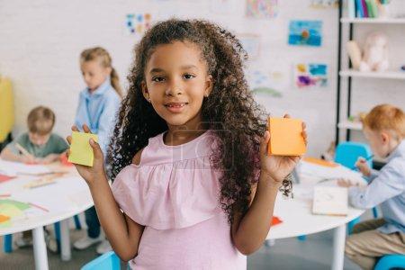 Photo pour Foyer sélectif de mignon enfant afro-américain avec des notes vides regardant la caméra avec des camarades de classe derrière en classe - image libre de droit