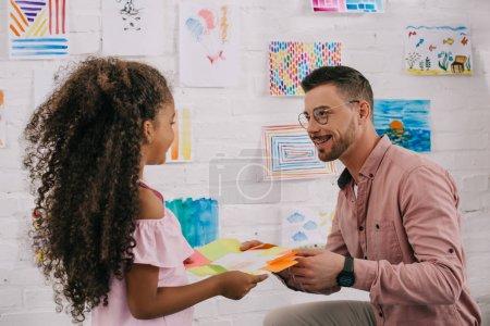 african american preschooler giving picture to smiling caucasian teacher in classroom