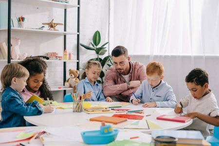 teacher and interracial preschoolers at table with paints and papers in classroom
