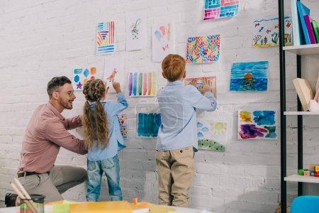 Photo pour Enseignant souriant aider les petits enfants d'âge préscolaire accrocher des images colorées sur le mur dans la salle de classe - image libre de droit