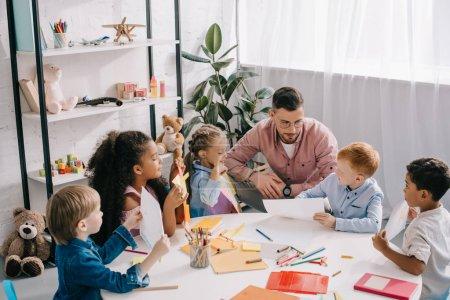 Foto de Maestra y niños interraciales en mesa con pinturas y trabajos en aula - Imagen libre de derechos