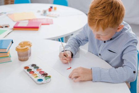 focused preschooler red hair boy drawing picture at table in classroom