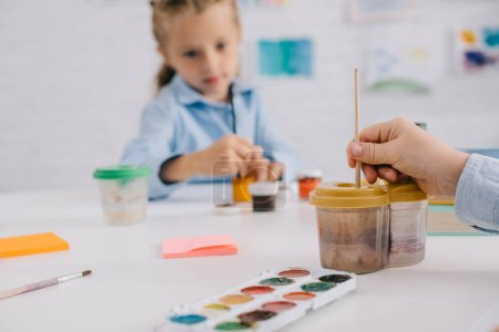 partial view of preschoolers drawing pictures with paints and paint brushes at table in classroom
