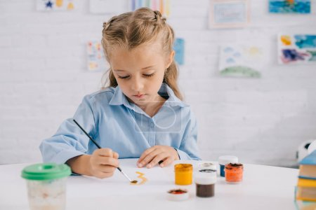 portrait of adorable focused child drawing picture with paints and brush at table