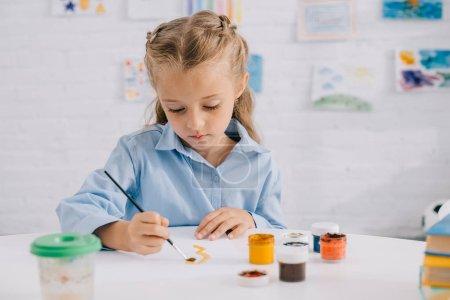 Portrait de l'adorable enfant ciblé dessin avec peintures et pinceau à table
