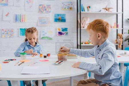 Portrait des enfants d'âge préscolaire mignons dessiner des images avec des peintures et pinceaux à table dans la salle de classe