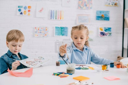 focused preschoolers drawing pictures with paints and paint brushes at table in classroom