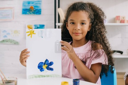 portrait of african american kid showing colorful picture in hands while sitting at table in room