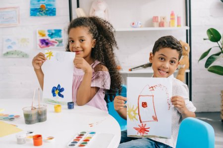 portrait of happy african american kids showing pictures at table in classroom