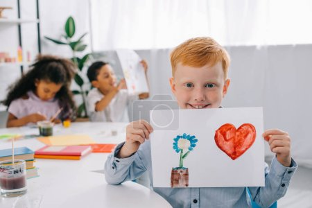 selective focus of smiling red hair boy showing picture in hands with african american classmates behind in classroom