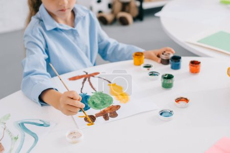 partial view of child drawing picture with paints and paint brush at table