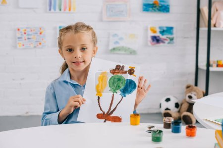 portrait of little kid showing colorful picture in hands while sitting at table in room