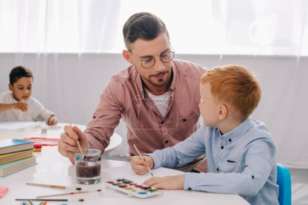 teacher helping little boy to draw picture at table in classroom
