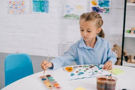 Portrait de l'adorable enfant ciblé dessin coloré avec peintures et pinceau à table