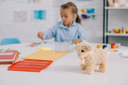 selective focus of toy sheep and kid drawing picture at table in room