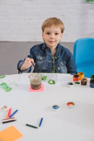 portrait of little boy sitting at table with paints and paint brush for drawing in classroom
