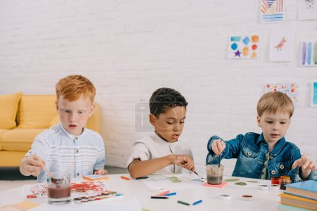 portrait of multiethnic kids with paint brushes drawing pictures in classroom
