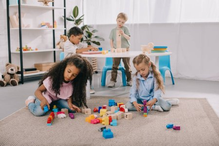 focused multiracial preschoolers playing with wooden blocks in classroom