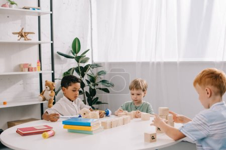 Photo for Multicultural little boys plying with wooden blocks at table in classroom - Royalty Free Image
