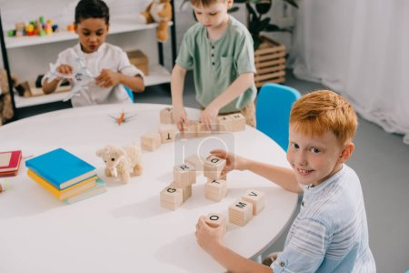 multicultural little boys plying with wooden blocks at table in classroom