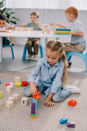 selective focus of multiracial preschoolers playing with blocks in classroom