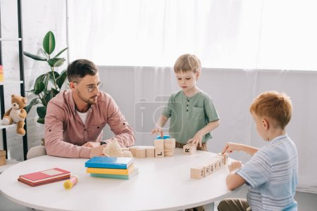 preschoolers playing wit h wooden block with teacher near by in classroom