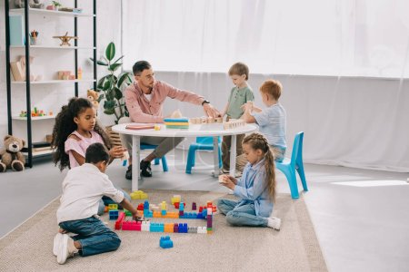 Photo for Teacher and multicultural preschoolers on floor with colorful bricks in classroom - Royalty Free Image