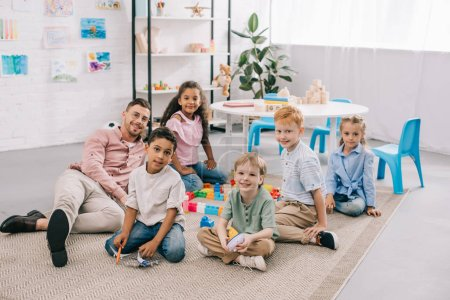 Photo for Smiling teacher and multicultural preschoolers sitting on floor with colorful bricks in classroom - Royalty Free Image