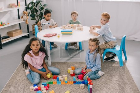 multiracial preschoolers looking at camera while playing with wooden blocks in classroom