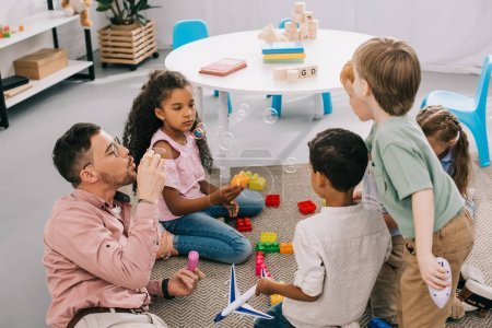 Photo for Teacher with soap bubbles and multicultural preschoolers sitting on floor with colorful bricks in classroom - Royalty Free Image