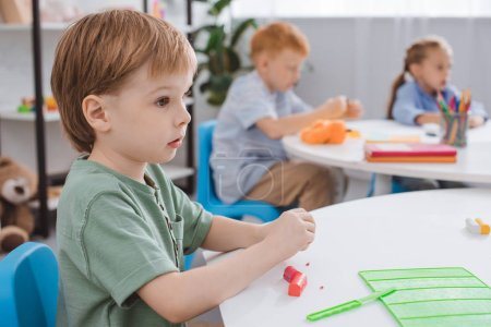 selective focus of adorable boy with plasticine sitting at table in classroom